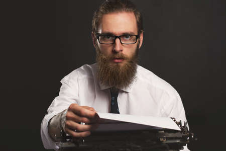 Handsome young hipster businessman thinking and writing with vintage typewriter. Old fashion style.