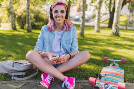 Attractive pretty European beautiful woman with pink hair in headphones listening to music from smart phone sitting in park on green grass background in a blue shirt. Female relaxing after skateboarding.