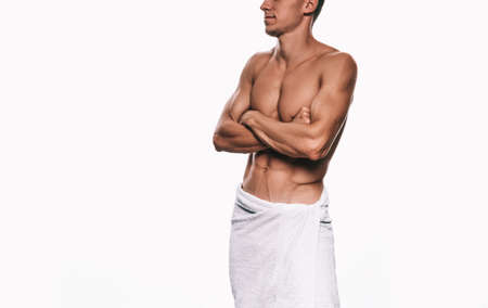 Image of young sportsman wrapped in white towel showing his sexy body while standing against white background. Shirtless athlete fit guy with sexy abdomen cross hands posing in studio. Healthy concept