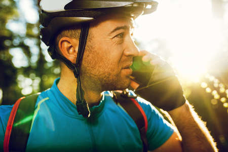 Close up portrait of young Caucasian cyclist in sportswear wearing helmet and blue t-shirt, talking on mobile phone with friend looking away, having small break while exercising outdoors in forest. Reklamní fotografie - 118642809