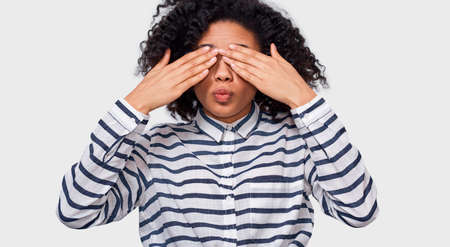Good-looking stylish African American young woman in striped shirt, covering eyes with palms and making air kiss, waiting to be kissed. Playful dark-skinned  female playing hide, seek and peek a boo. Stok Fotoğraf - 119244864