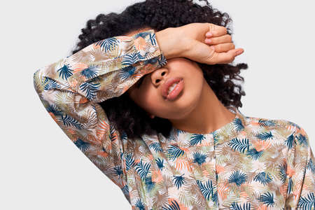 Portrait of dark skinned young woman covering eyes with her arm, dont want to see someone. African American girl putting her hand over forehead has tired feelings. People emotions concept