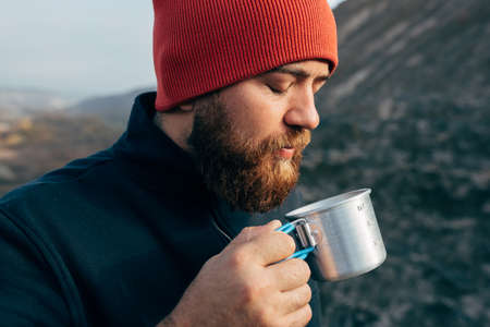 Close up outdoors portrait of young man drinking hot beverage in mountains, relaxing after trekking. Traveler male in red hat, holding a mug of tea after hiking. Travel, people, sport and lifestyle Banco de Imagens
