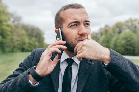 Portrait of handsome young urban European professional man using mobile gadget outdoors. Trendy looking entrepreneur making business call, talking on smart phone to his partner, having serious look.