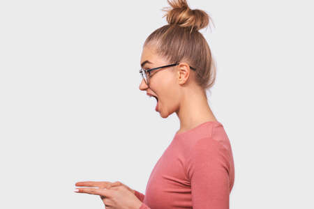 Side view image of amazed woman in eyewear, indicates aside with fore fingers to blank copy space, isolated over white wall. Caucasian female with hair bun wearing pink blouse with widely opened mouth Banco de Imagens