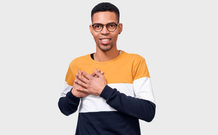 Candid portrait of kind dark-skinned man keeps both palms on chest, expresses kindness. Afro male looks directly to camera, in casual outfit, isolated over white background. People and body language Фото со стока