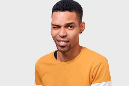 Indoor close up portrait of handsome African American young man with positive expression, blinks eye and smiles happily. People, lifestyle, facial expressions and emotions concept