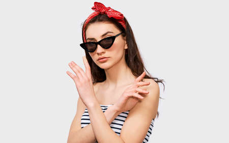 Beautiful young brunette woman making stop gesture with her hands. Pretty girl wearing summer striped blouse, black trendy sunglasses and red headband, making rejection gesture, posing on white wall Standard-Bild