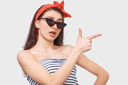 Image of amazed young brunette woman in trendy sunglasses, indicates aside with forefinger to blank copy space, isolated over white wall. Caucasian girl wearing striped blouse with opened mouth. Standard-Bild