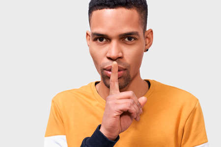 Close up portrait of serious African American man wearing yellow sweater, keeps fore finger on lips, making shh gesture for secret or be quiet. Dark-skinned stylish male shows silence sign. People