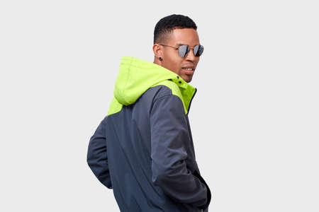 Rear view of stylish mixed race man looks with concentrated expression, wearing green hoody, looking through mirror glasses. African American male posing on white studio wall. People and emotions Imagens