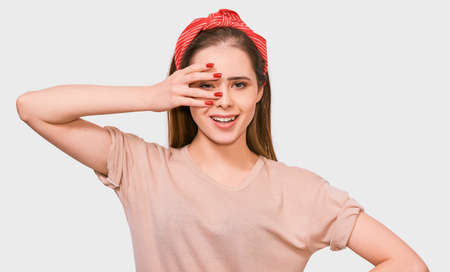 Beautiful young woman hiding her face with palm, showing her eye. Studio portrait of pretty female covering her face by hand wearing beige t-shirt, red headband, looking at camera posing on white wall