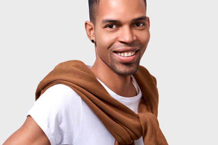 Horizontal close up portrait of handsome dark-skinned man smiling wears casual stylish outfit, looking to the camera. Succesful African American businessman posing on white studio wall. People emotion