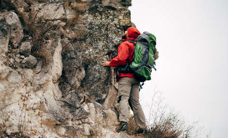 Rear view image of young man hiking in mountains dressed in red clothes exploring new places. Traveler bearded male trekking and mountaineering during his journey. Travel, people, sport, lifestyle Reklamní fotografie
