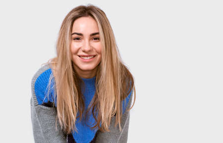 Charming friendly-looking European young woman in stylish loose sweater, smiling broadly and looking to the camera, isolated over white background. People emotions concept