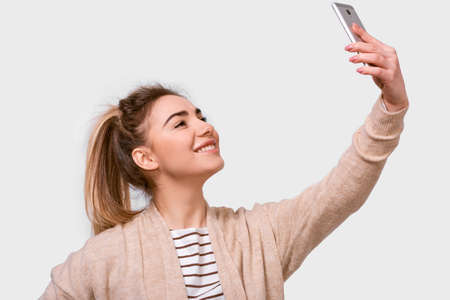 Side view studio shot of a pretty young European woman in casual clothes smiling to her boyfriend while speaking online. Lovely female taking a selfie isolated over white studio background.