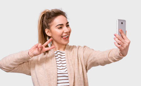 Studio image of a happy young European woman in casual clothes showing tongue and peace sign, taking a selfie isolated over white studio background.