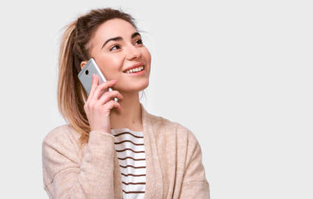 Horizontal indoor shot of young pretty woman smiling and talking on cellphone to her friend, looking up cheerful and happy, posing on white studio background. Real human emotions 版權商用圖片