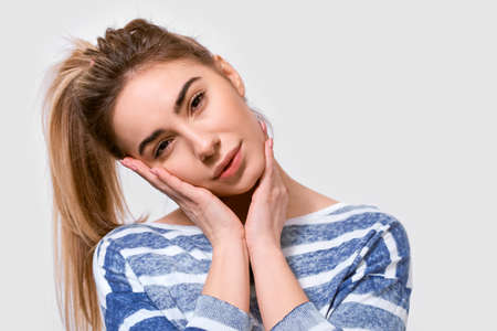 Pretty young woman in stylish striped sweater with pleasant expression, looking to the camera, isolated over white background. People emotions 版權商用圖片