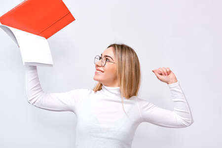 Studio portrait of happy young businesswoman wearing white blouse and round trendy eyeglasses with red folder in hand, with blank copy space for your text.