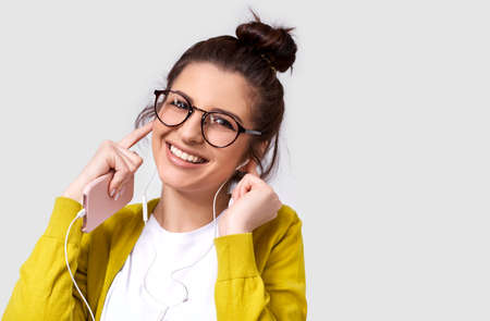 Studio horizontal portrait of pretty happy young woman smiling broadly, using cellphone to listening the music. Happy female enjoying the favorite songs via smart phone on earphones.