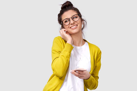 Studio horizontal portrait of candid smiling woman in round eyewear, touching earphones. Indoor shot of Caucasian young female with shiny skin wears yellow blouse and white t-shirt, enjoy the music.