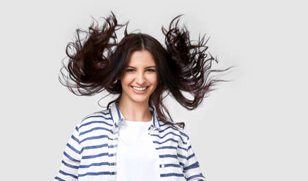 Studio shot of beautiful joyful brunette woman with flying hair smiling broadly, looking directly at the camera, posing over white background. People real emotions 版權商用圖片