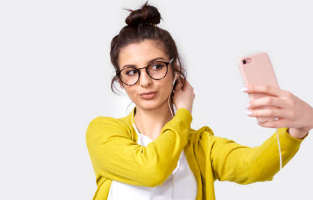 Shot of young European woman student in casual clothes, taking self portrait over white studio wall. Happy female posing and taking a selfie on her smart phone, isolated over gray background. 版權商用圖片