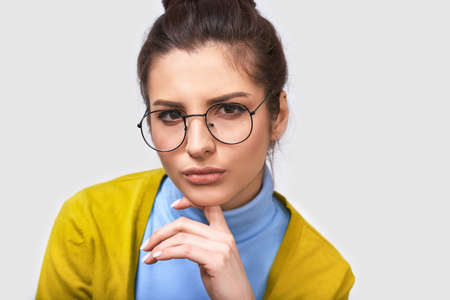 Serious young businesswoman wearing blue blouse and round transparent eyeglasses, with white blank copy space for your text. Close up portrait of European female office worker posing on white wall. 版權商用圖片