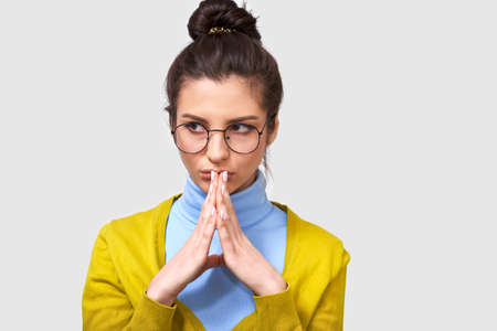 Stylish female, makes up plan, keeps palms together, looking aside, wears yellow sweater and blue blouse, round eyewear, poses against gray background, has intriguing look. Body language concept Imagens