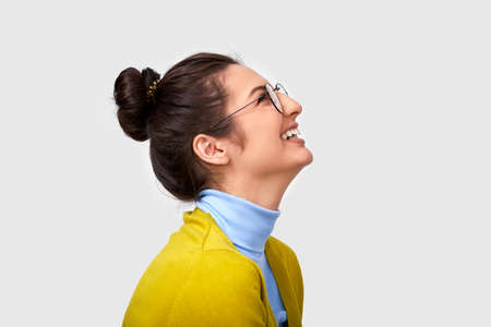 Candid side view studio portrait of beautiful young woman, smiling broadly, wears casual outfit and spectacles, looking up to blank copy space. Caucasian brunette female in yellow blouse on white wall 版權商用圖片
