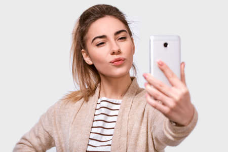 Studio close up studio shot of a pretty young European woman in casual clothes sending air kiss to his boyfriend while standing and taking a selfie isolated over white studio background. 版權商用圖片