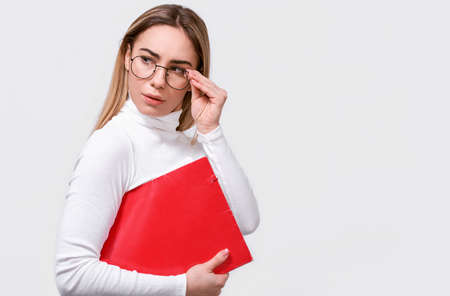 Serious young businesswoman wearing white blouse and round trendy eyeglasses with red folder in hand, with blank copy space for your text. European female office worker posing on white studio wall. 版權商用圖片 - 122817841