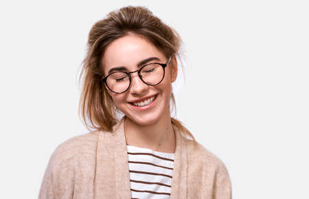 Horizontal close up portrait of dreamful positive female in casual outfit and eyewear, smiling with closed eyes, imagines something pleasant, posing over white background. People positive emotions 版權商用圖片 - 122817844