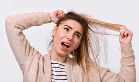 Close up image of upset young woman trying comb unruly hair pulling strands with raised hands screaming from pain and discomfort,  posing over white background. People, health and care concept