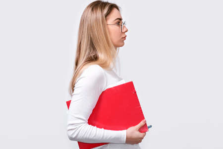 Side view of serious young woman wearing white blouse and round trendy eyeglasses with red folder in hand, looks away to blank copy space. European female office worker posing on white studio wall.