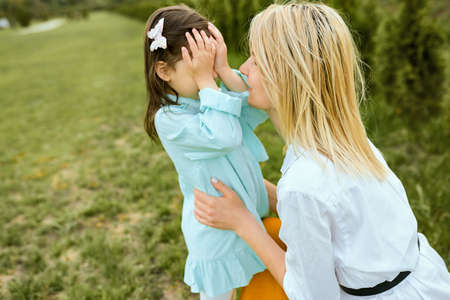 Pretty kid playing hide-and-seek with young mother outdoor. Portrait of joyful woman and her cute child playing in the park. Mother and daughter shares love. Happy Mothers Day. Motherhood, childhood