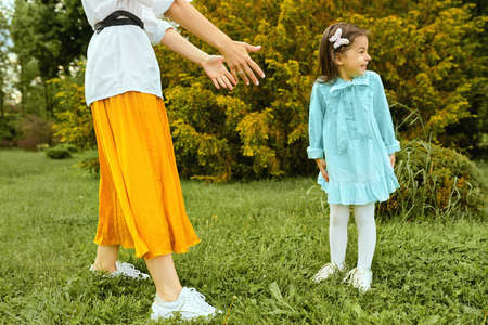 Young woman and cute child playing and smiling in the park outside. Happy kid having fun with mother on the green grass. Mother and daughter shares love. Happy Mothers Day. Motherhood and childhood