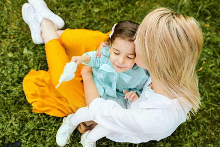 Outdoors image of beautiful mother kissing and cuddling with her daughter, enjoying the time together. Cute little girl embraces her mom, sitting on the green grass in the park. Mothers day 版權商用圖片