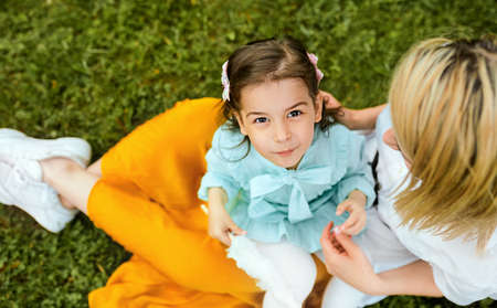 Top view image of happy kid playing with her mother, enjoying the time together outdoors. Cheerful little girl eating cotton candy with her mom, sitting on the green grass in the park. Mothers day. 版權商用圖片