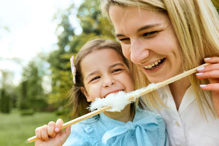 Closeup portrait of happy little girl having fun and eating cotton candy with her mother in the park. Young woman laughing and playing with her joyful daughter, enjoying the time together. Mothers day Banque d'images