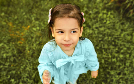 Outdoor horizontal image of cute child smiling and playing in the city park. Beautiful little girl wearing light blue dress, having fun outside and posing on the green grass in the summer holiday.
