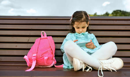 Outdoors horizontal image of toddler girl playing with smartphone sitting on bench in the city park. Curious cute little girl playing games on her mobile phone. Technology, education and lifestyle. 版權商用圖片