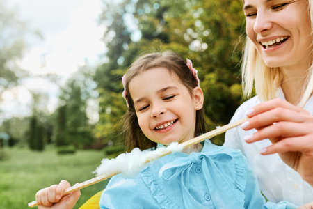 Candid image of happy little girl having fun and eating cotton candy with her mother in the park. Young woman smiling and playing with her joyful daughter, enjoying the time together. Mothers day.