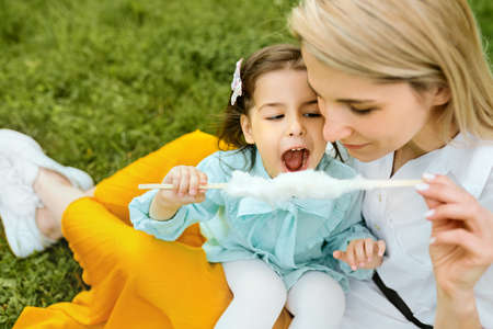 Cheerful little girl eating cotton candy with her mom, sitting on the green grass in the park. Happy kid daughter playing with her mother, enjoying the time together outdoors. Mothers day.