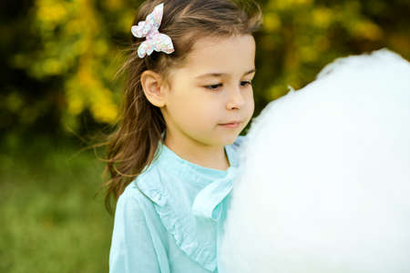 Closeup outdoor portrait of sweet child eating white cotton candy in the city park. Beautiful little girl wearing light blue dress, having fun outside and posing on the green grass in the summer.