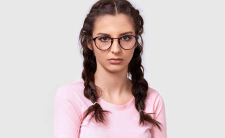 Indoor closeup portrait of overworked young brunette woman has tired facial expression, wears eyewear and pink casual blouse, isolated over white background. Shot of pretty sad female over gray wall