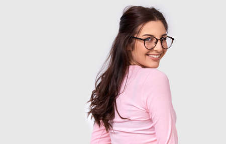 Horizontal studio image of beautiful young woman, smiling broadly, wearing pink casual outfit and eyeglasses. Caucasian brunette female feeling happy, posing over white studio wall. People and emotion