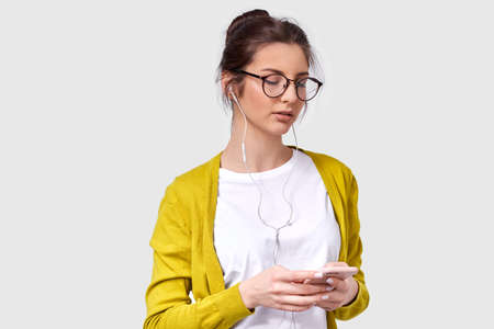Studio horizontal shot of candid young woman in eyeglasses enjoy the favorite songs from earphones, using smart phone. Caucasian young female with shiny skin wears yellow blouse and white t-shirt.