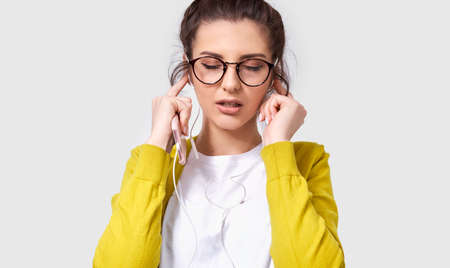 Candid horizontal shot of brunette pretty young woman using mobile phone to listening the music. Beautiful female enjoy the songs on earphones using her smart phone. People and technology concept
